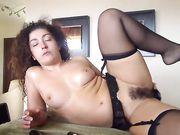 Une femme mature avec une chatte poilue se masturbe devant la caméra